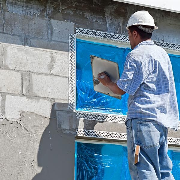 man applying cement stucco to home exterior