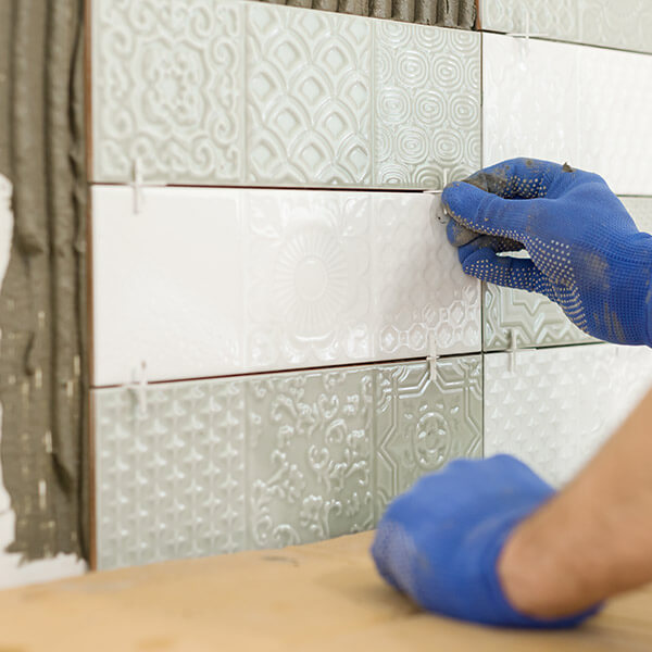 close-up of tiles being installed as backsplash