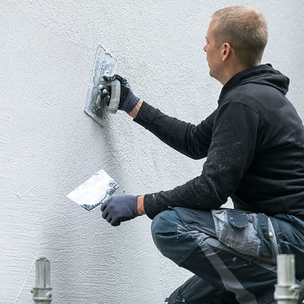 man applying stucco exterior